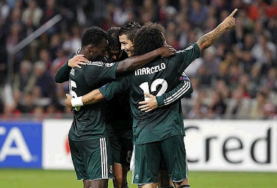 Real Madrid players wearing the green jersey celebrate a goal against Ajax