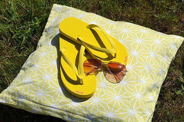 Sonnengelbes Ikea-Kissen mit quetschgelben Flip-Flops, Farben des Sommers