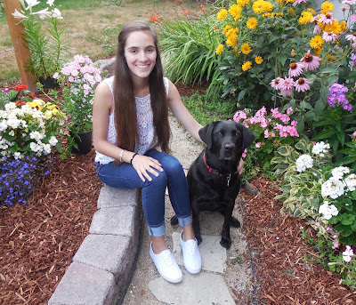 Mikaela sits smiling on a rock path (surrounded by beautiful flowers) with her arm around a black Lab.
