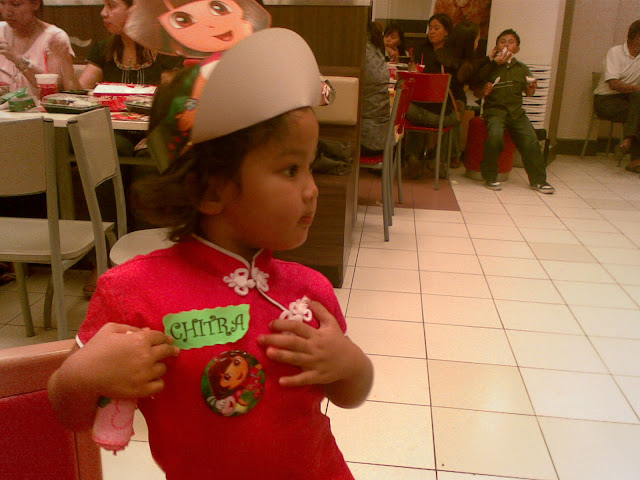 Kecil looking on in her Dora hat