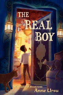 Book cover, 'The Real Boy' by Anne Ursu. From a darkened hallway, a young boy carrying a lantern enters a room with vials on tables and attached to the wall. Behind him, cats peer into the room he has entered.