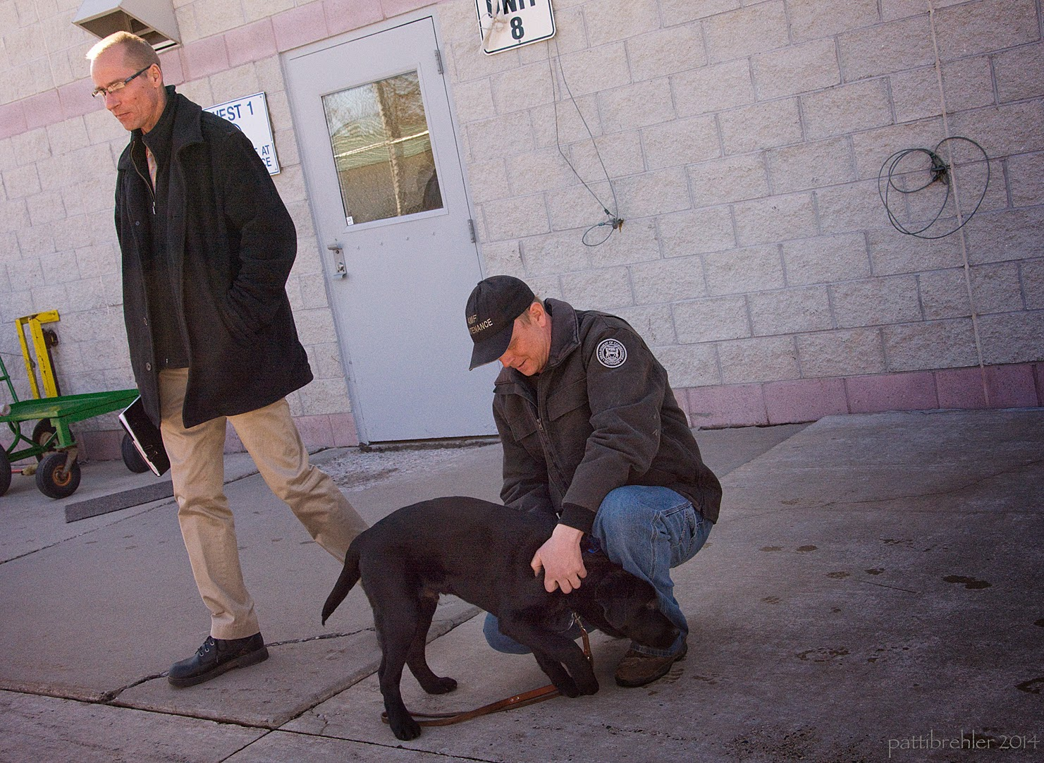 A man with glasses wearing a dark pea coat and khakis is walking to the left of the picture. A second man is squatting on the cement, he is wearing a black baseball cap and dark jacket and blue jeans. He is lookig down at a black lab puppy that is standing in front of him with its head low by his left leg. The man is touching the puppy's body with his hands. The puppy has a leash dragging behind him.