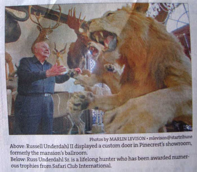 Newspaper photo of an older man among taxidermied antelopes and lions