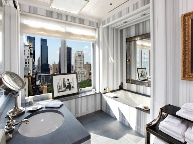 master bathroom with step in tub, window with a view of Central Park, black counter tops and striped marble walls