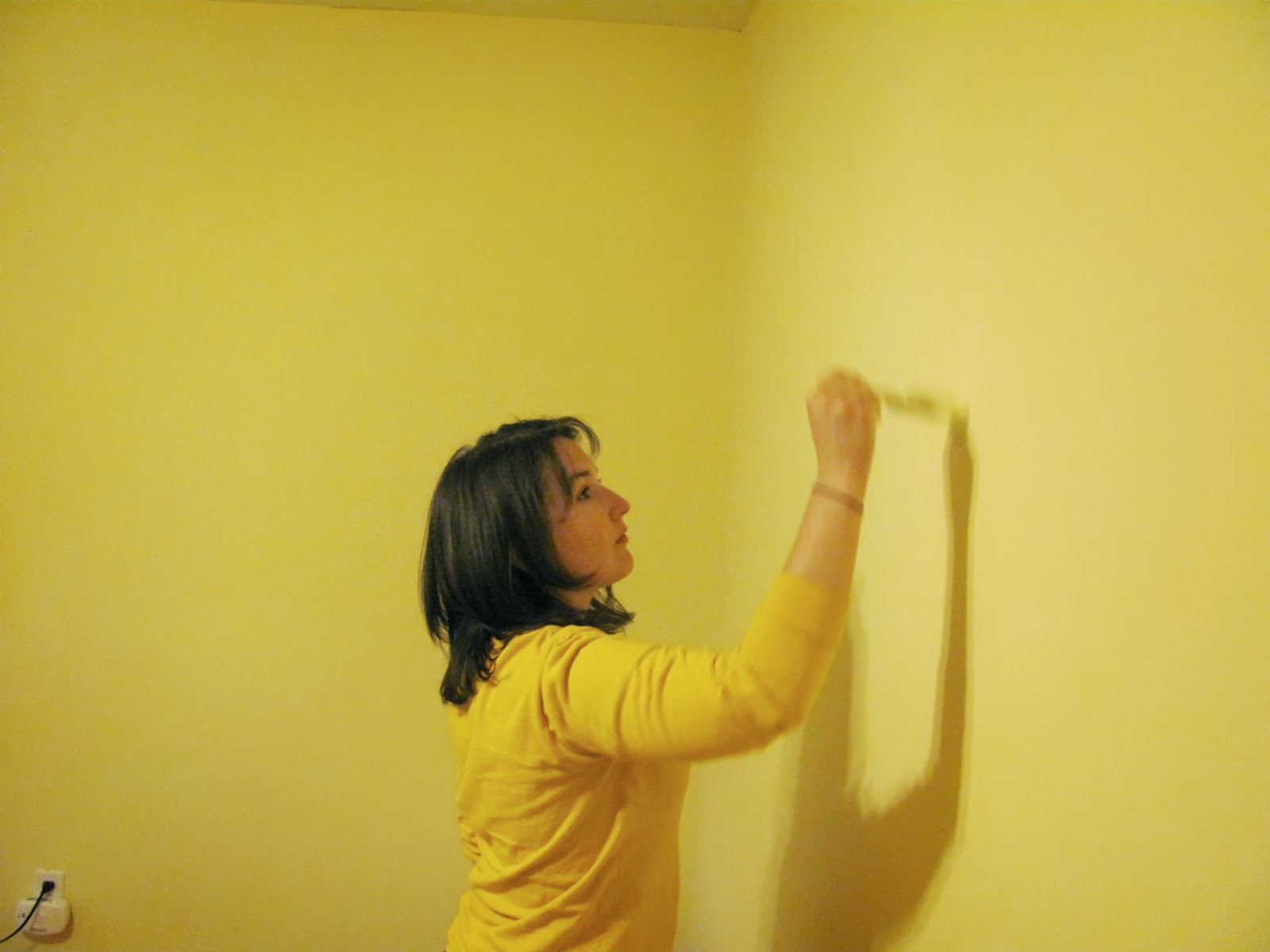 Sara touches up the paint in the bedroom after taking down the pictures on the wall
