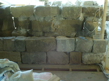 Part of the stone wall in the 2 bedrooms behind the steeple being relayed