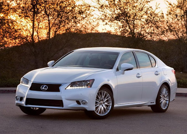 White 2013 Lexus GS450h front three-quarters view at dusk with trees and hills