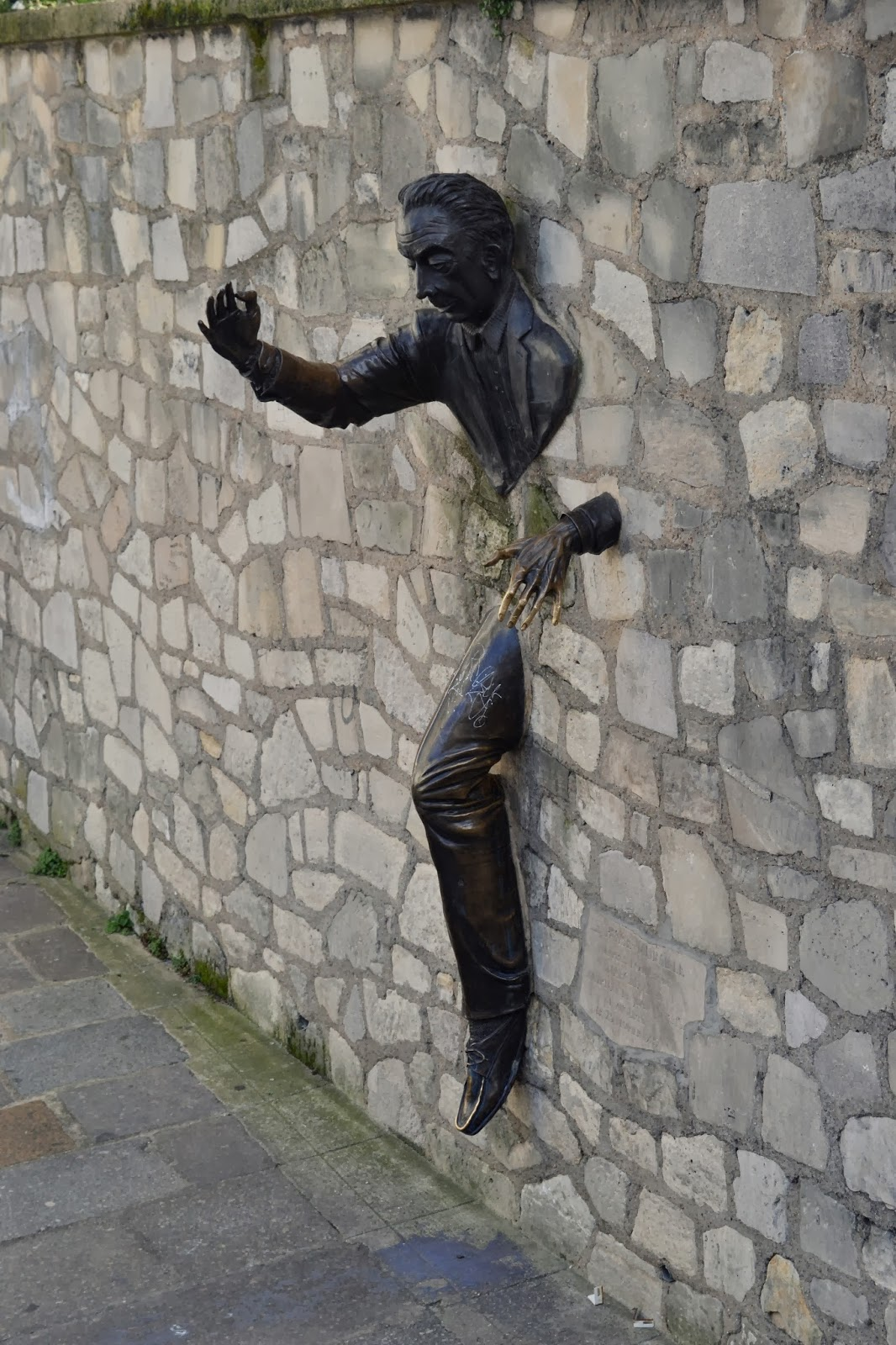 Statue of a man coming out the wall Paris