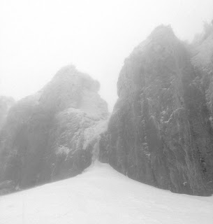 A big couloir socked in with fog.