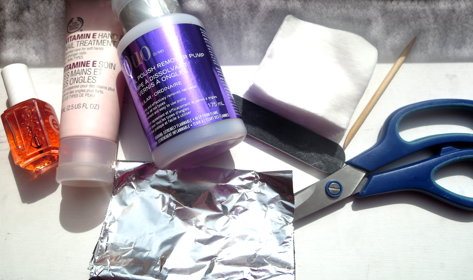 a picture of cuticle oil, hand cream, acetone remover, cotton pads, foil paper, scissors, cuticle stick