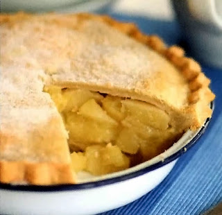 Deep double crust pear and apple pie with a wedge taken out to show the filling