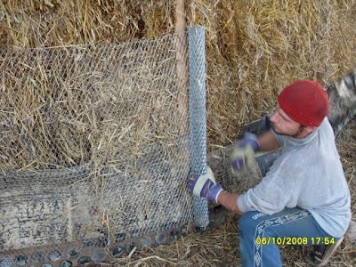 Обтягивание металлической сеткой каркаса соломенного дома.