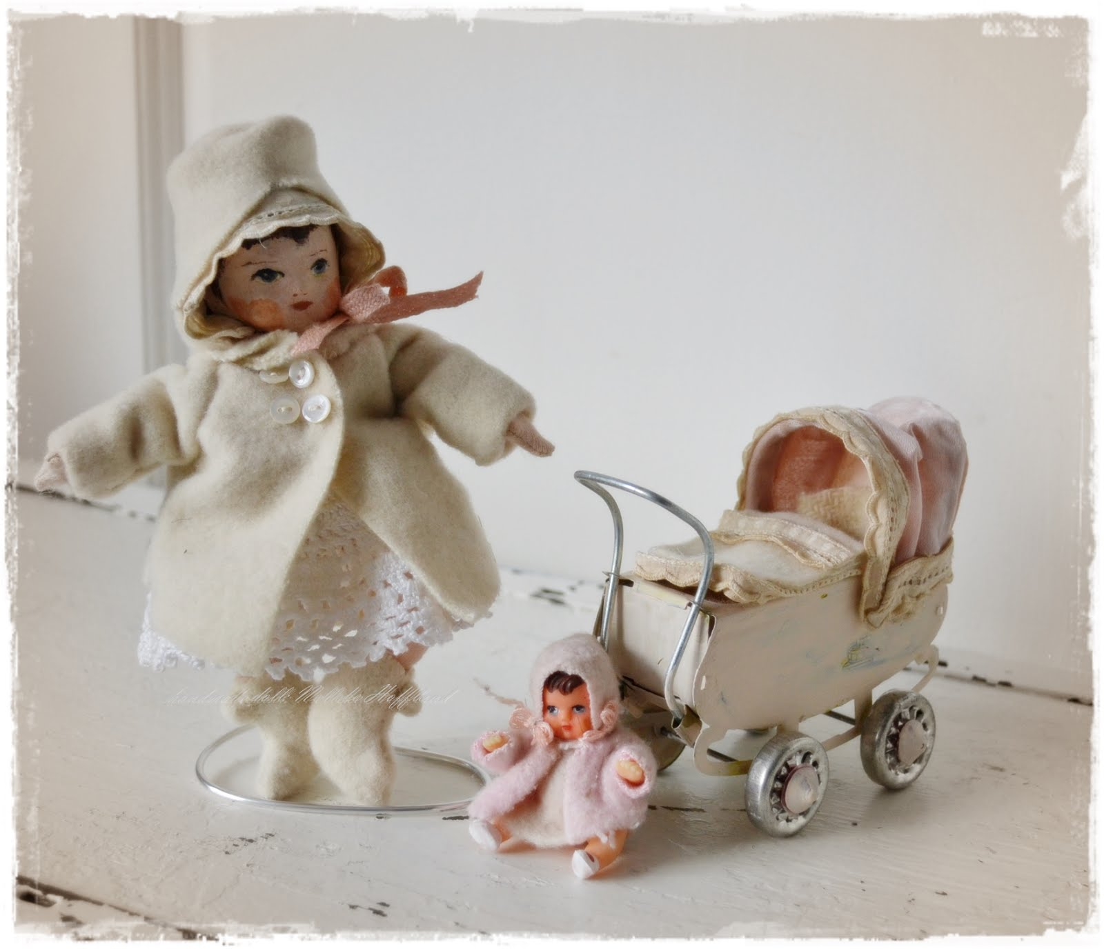 Klein popje met poppenwagentje