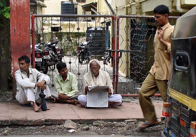 group of elderly men reading newspaper
