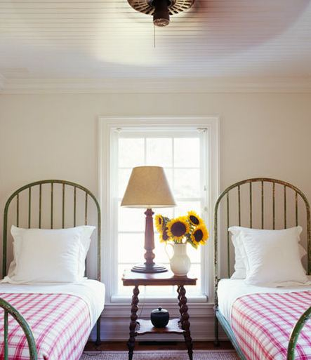 Bedroom with two twin beds with high arched iron bed frames