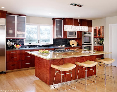 a modern kitchen occupying one wall side completes with a kitchen island