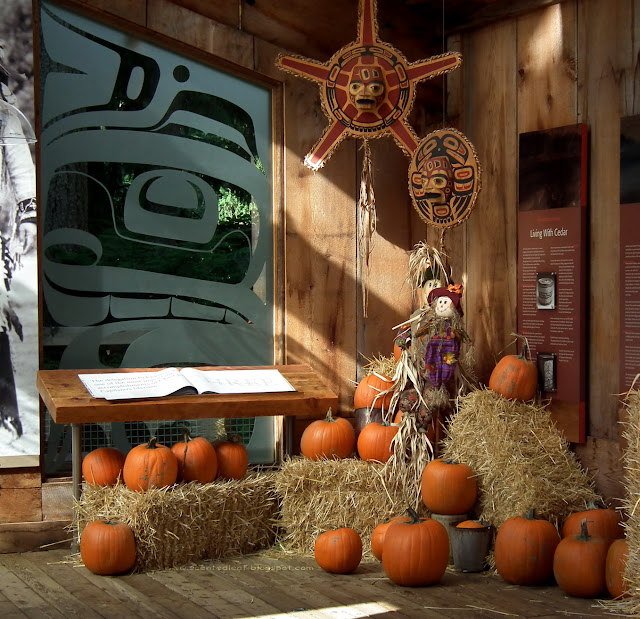 Fall- themed decorations:  pumpkins, hay, corn-shock, scarecrows at Capilano Suspension Bridge Park, Vancouver
