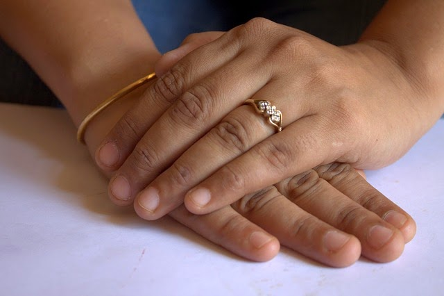 image woman's hands folded with wedding ring short fingernails