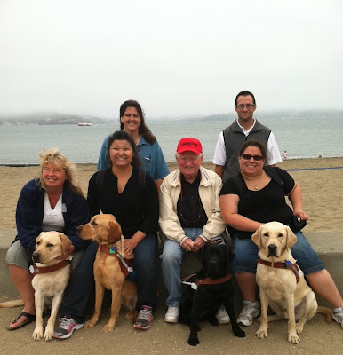 Sherry Downie with yellow Lab Rocco, Cristina Jones with yellow Lab Kingsley, Don Harlin with black Lab Valerie and Sasha Rangel with yellow Lab Rocky along with GDB Instructor Gin Meyer and Training Class Supervisor Adam Waskow