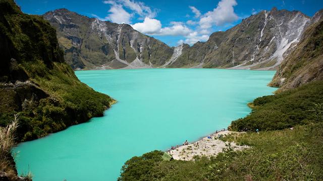lago de forma irregular com água verde clara cercado de rochas