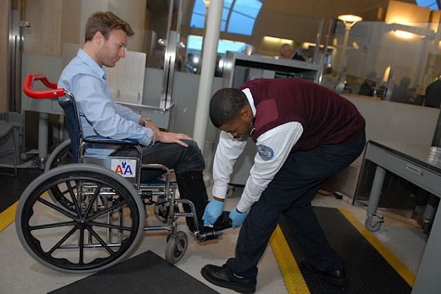man in wheelchair at airport secutiry and TSA person is wearing blue gloves and checking the man's feet.