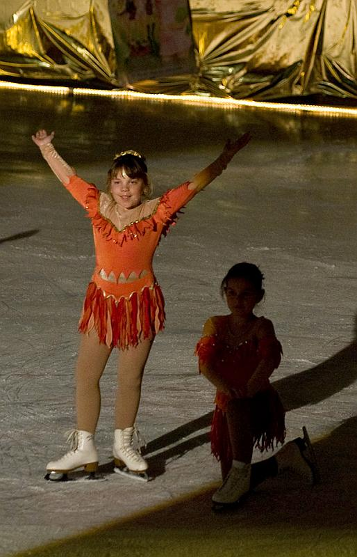 Young girls in costume at a figure skating event.
