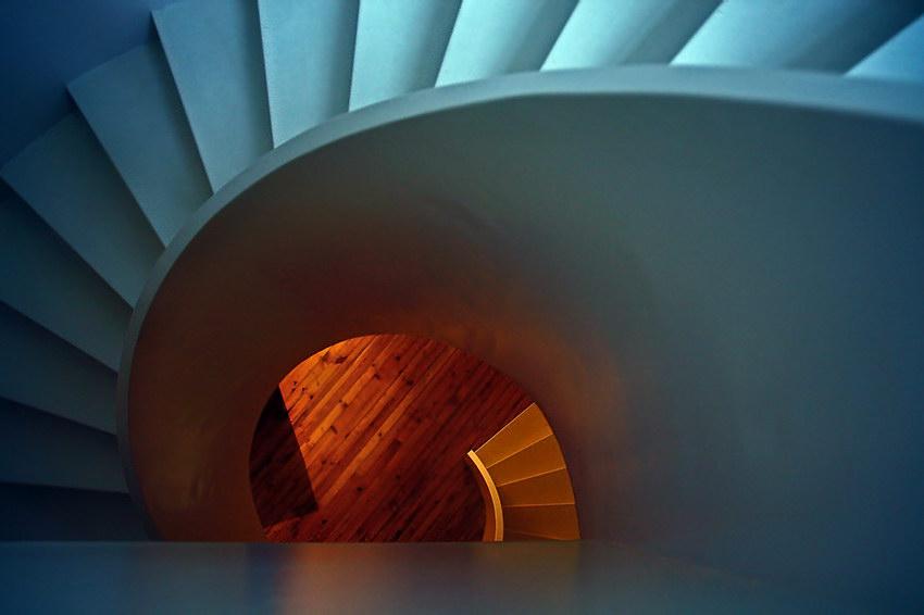 Grafismo duma escada em caracol, vista de cima. Imagem em tons azulados