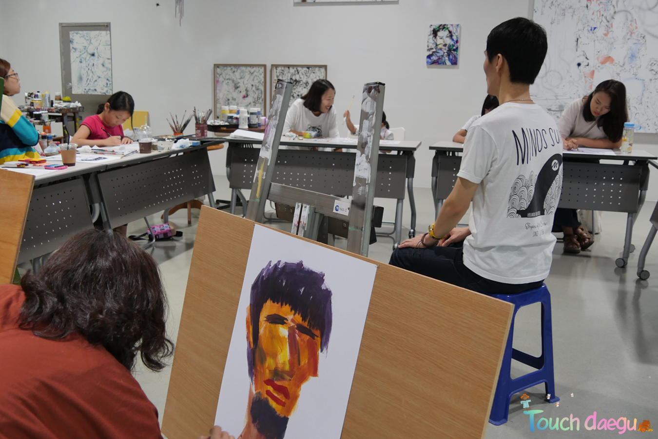 People are draqing a men in Daegu Art Factory
