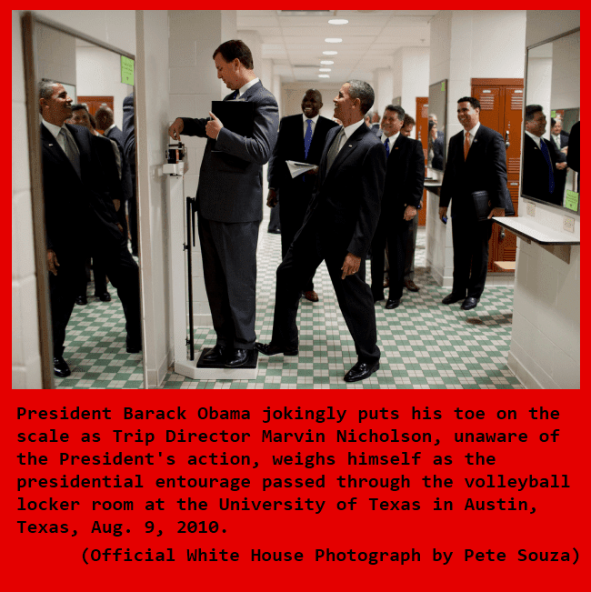 President Barack Obama jokingly puts his toe on a scale