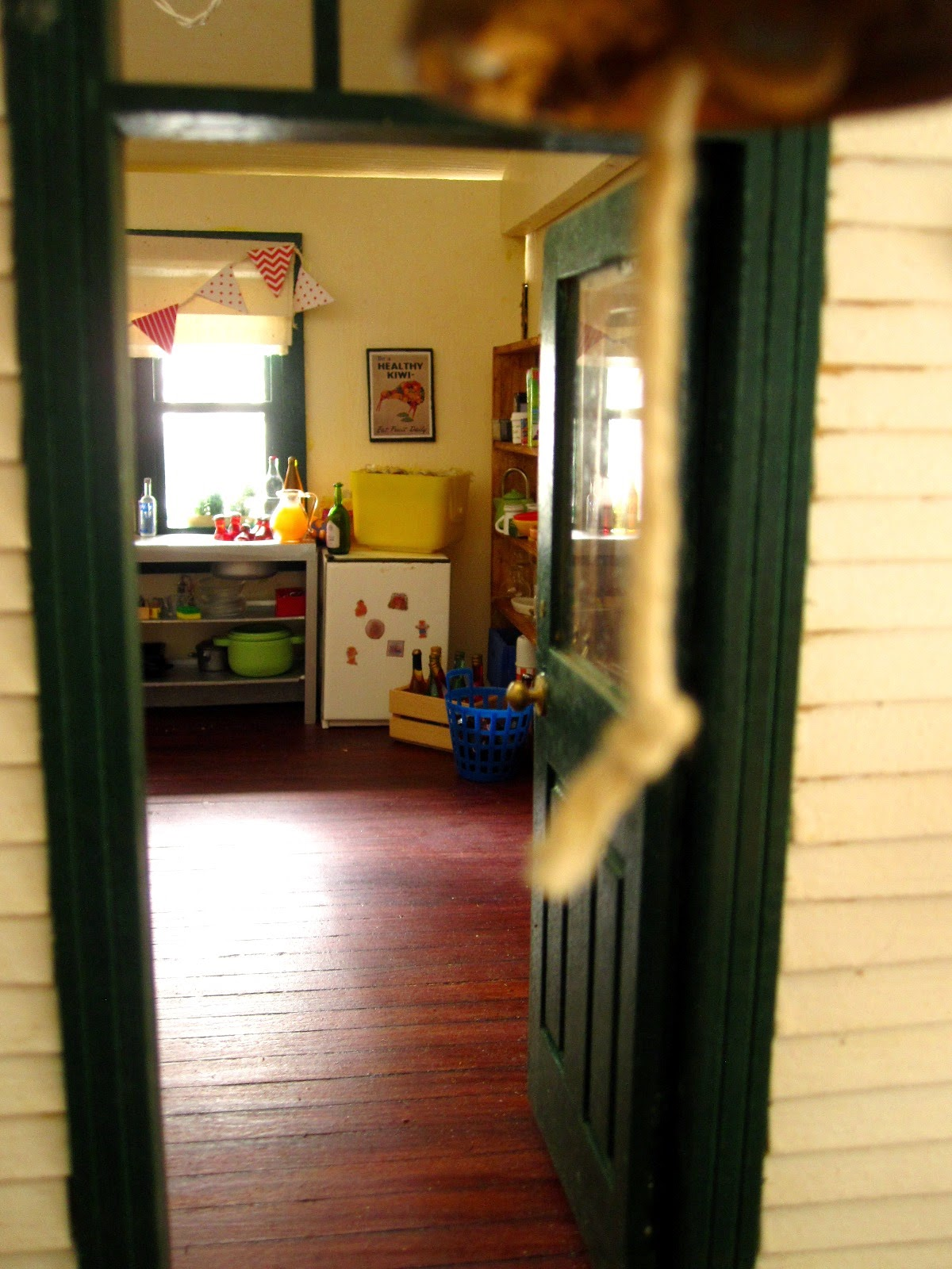 View through the front door of a miniature dolls' house school, showing the kitchen with a selection of drinks arranged.
