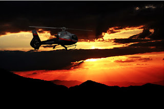 View of helicopter with the fiery sunset in the background.