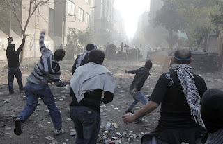 Egyptian protesters clashes with riot police along a road which leads to the Interior Ministry