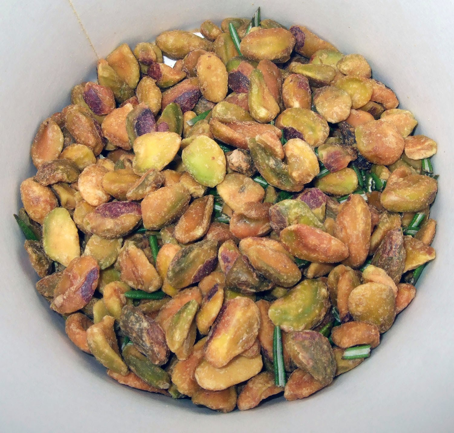 Pistachios and rosemary in container.