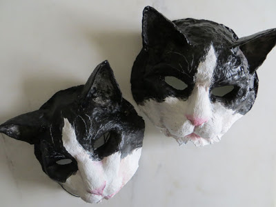 two paper mache masks cats by artist Shannon Reynolds
