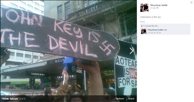 Skate board written in chalk 'John Key is the Devil' with a swastika next to it.  At a protest with an 'Aotearoa is not for sale' sign.