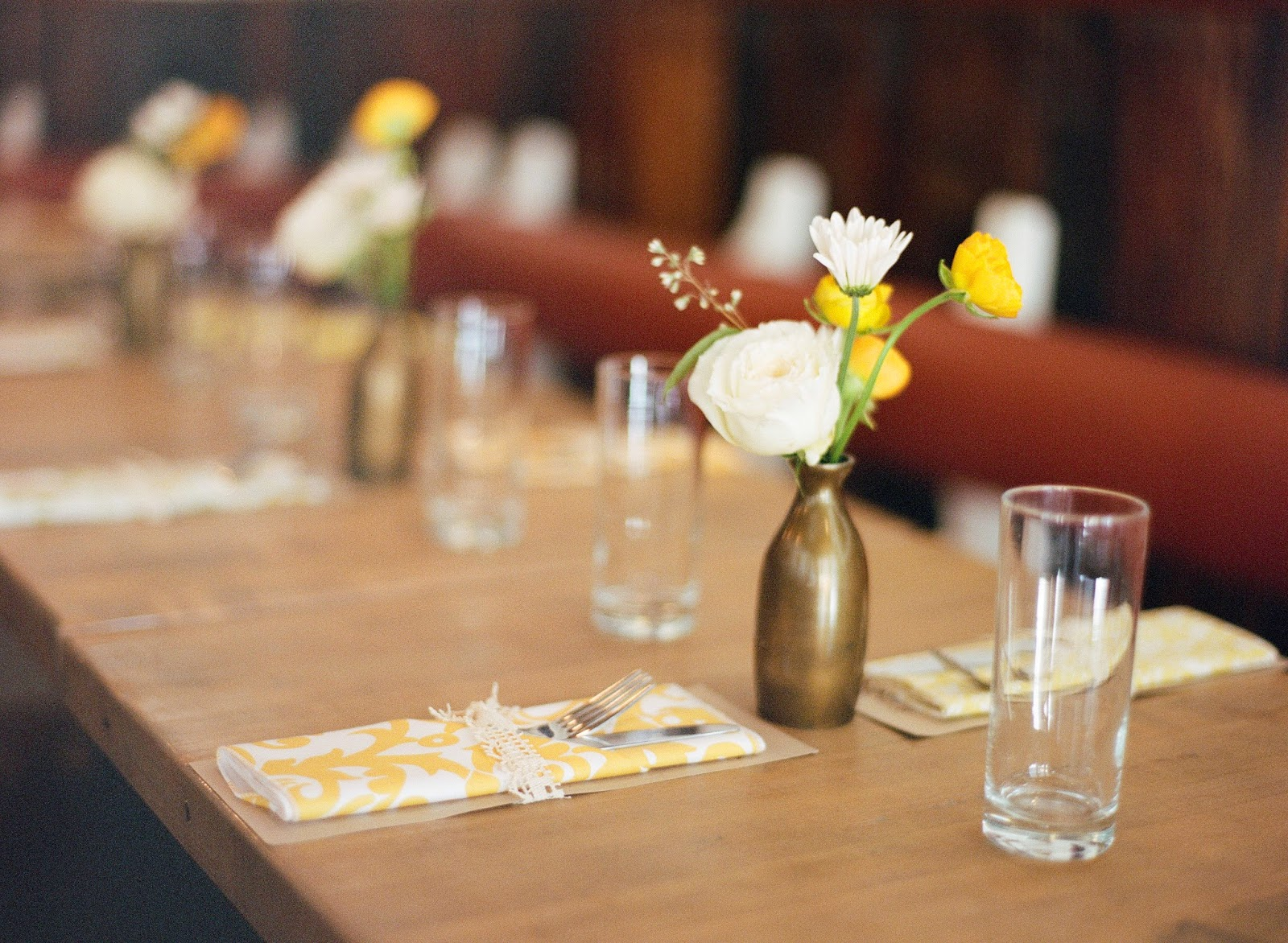yellow and white spring wedding flowers in antique brass vases with homemade yellow napkin place settings at an intimate brooklyn, new york restaurant wedding dinner