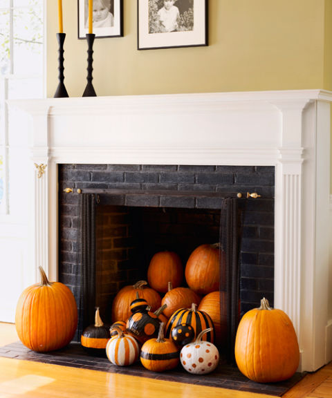 I love this easy, creative idea to decorate an unused fireplace for  Halloween. Purchase enough pumpkins in various sizes to stack inside your  firebox.