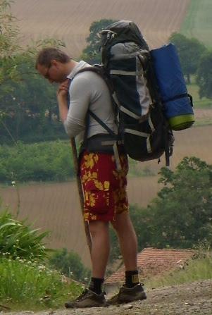 poutník Jan Bím s batohem opřený ohůl v prostřed cesty