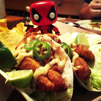 Tiny Deadpool, a bobblehead covered in a red bodysuit and brandishing a gun and a katana, stands in a pile of tortilla chips. In front of him are two catfish tacos topped with jalapenos, lime wedges, and creamy sauce.