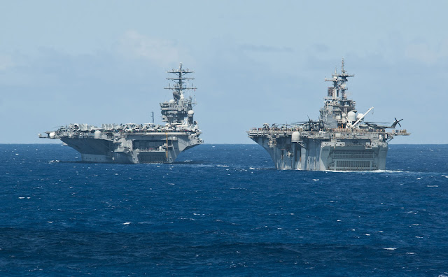 The aircraft carrier USS Nimitz (CVN 68) and the amphibious assault ship USS Essex (LHD 2) are underway in close formation