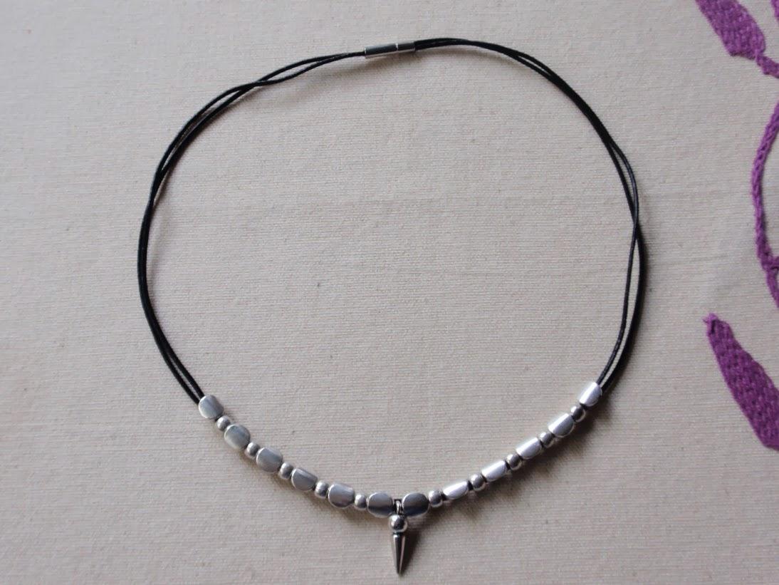 Collar  corto de chico en cuero negro con abalorios plateados planos y colgante central en forma de cono invertido