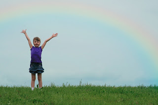 little girl in front of a rainbow