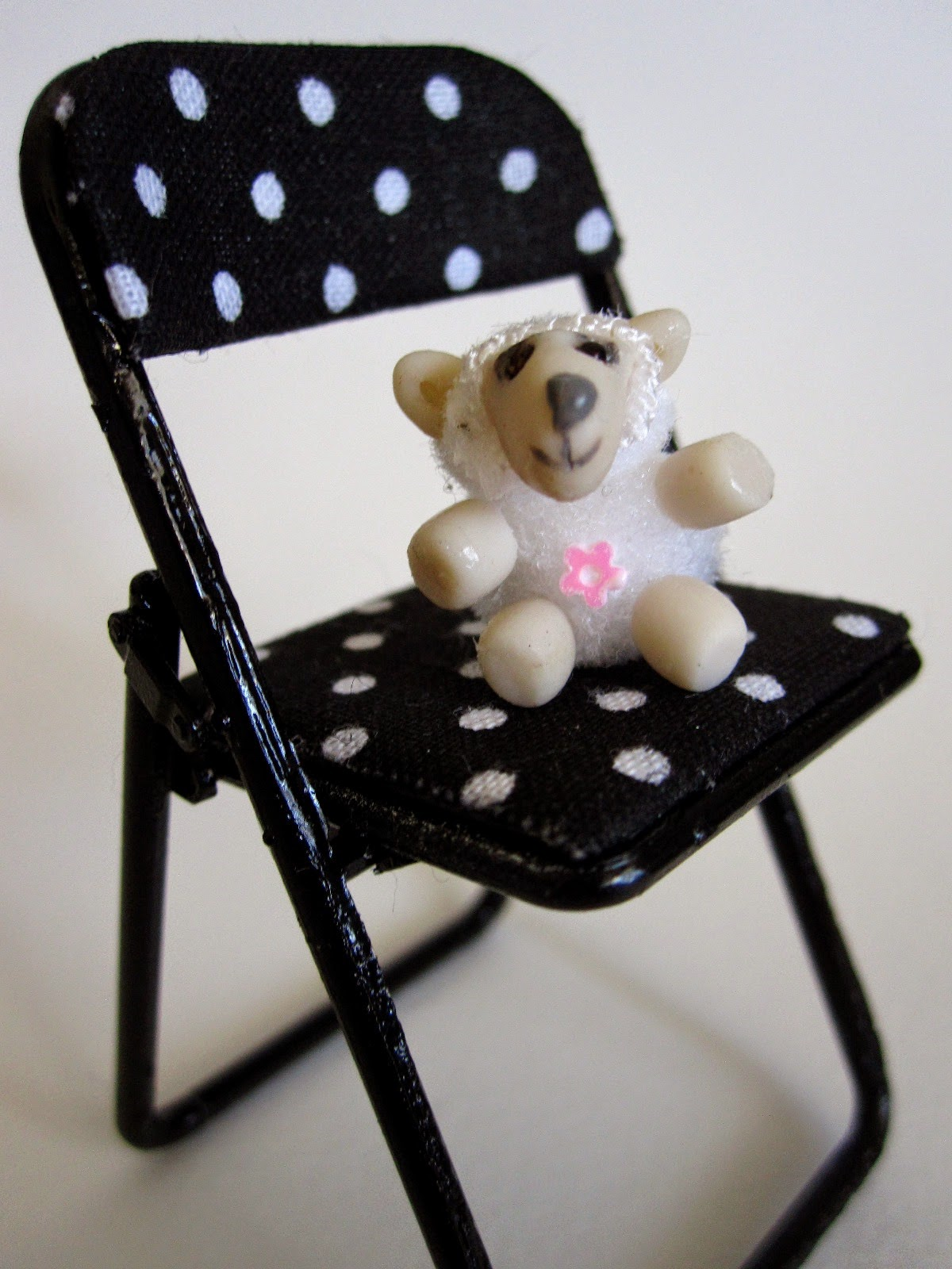 Modern dolls' house miniature stuffed toy sheep sitting on a miniature black and white spotted folding chair.
