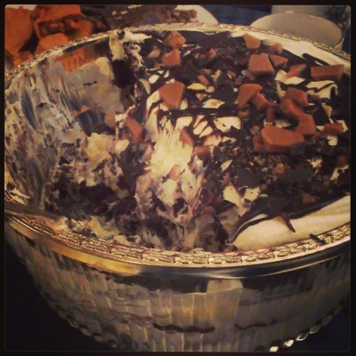 Photo of a trifle bowl with half the trifle scooped out.