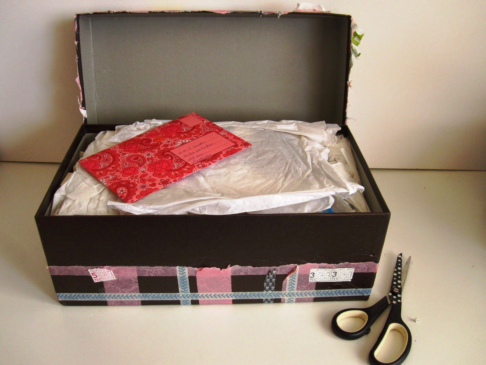 Large washi tape-wrapped shoebox with lid off, showing tissue paper and a colourful envelope on top of it.