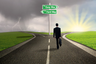 A businessman is at the fork of the road...one goes the easy way and the other the hard way