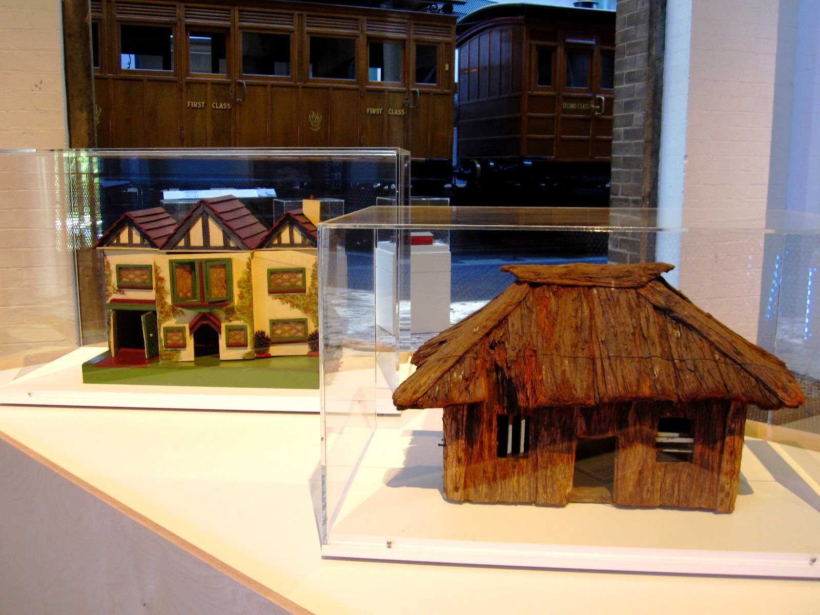 A vintage doll's house and model hut on display in a museum.