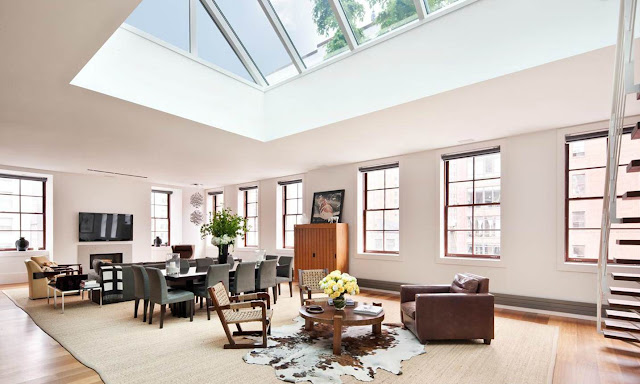 open plan living room in a NYC penthouse with a massive skylight, wood floors and windows