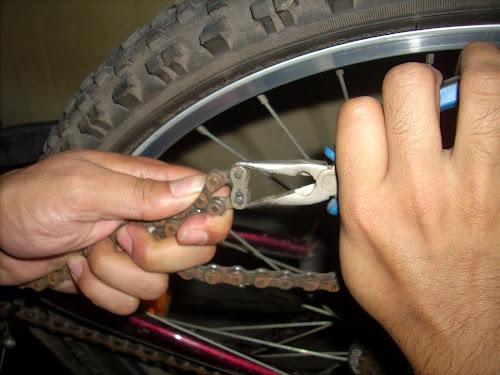 Nose pliers forcing together the pins on the quick link of a bicycle chain