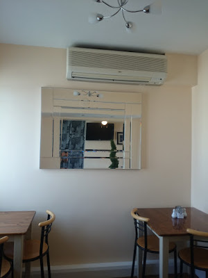 magnolia-cream cafe interior with wall mounted blower heater, and mirrors facing each other